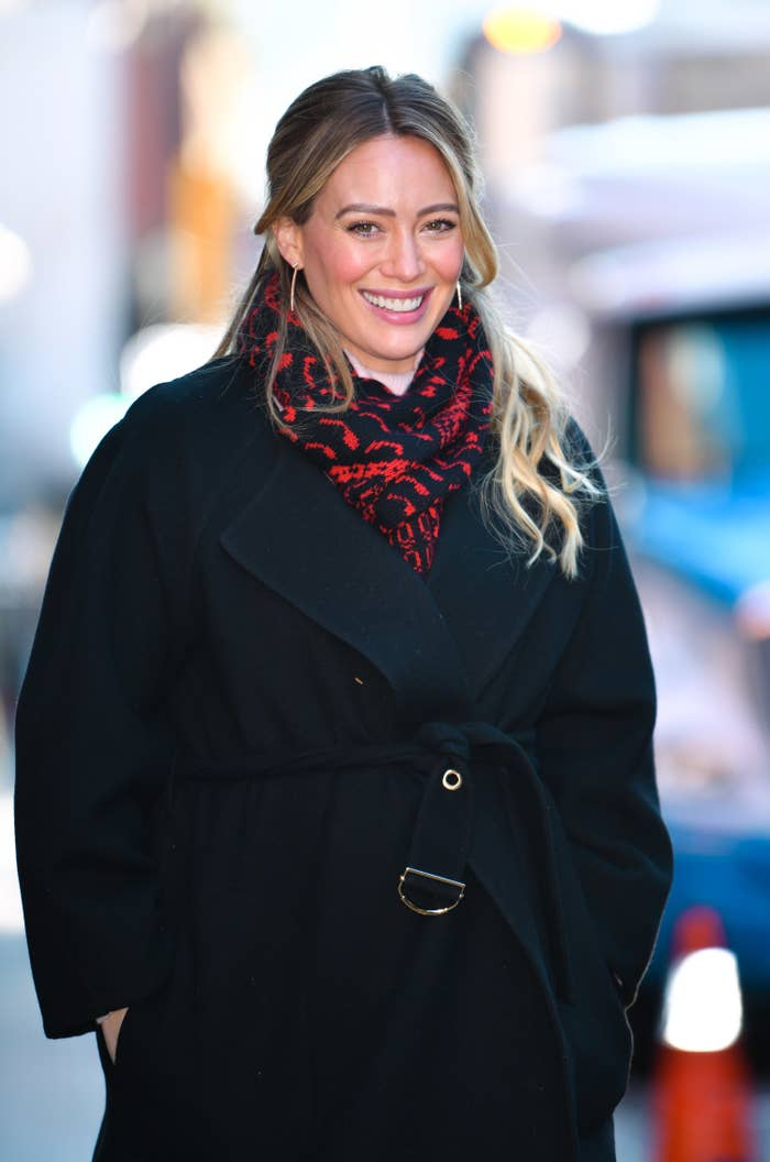 Hilary Duff in a trench coat and her hands in pockets