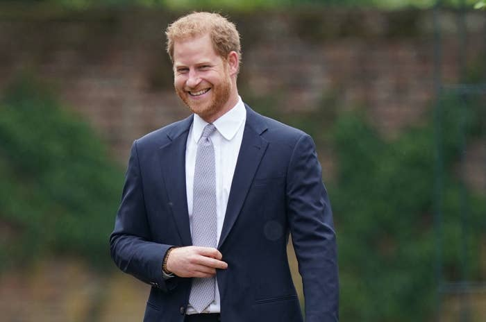 Prince Harry wearing a suit and smiling for the cameras