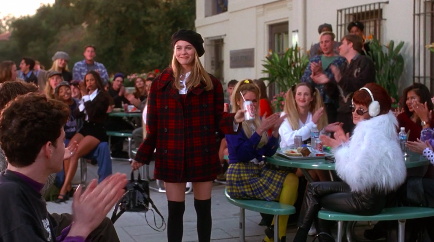 Cher wearing thigh-high socks, a button-up, a dress on top of it, a matching jacket, a necklace, a hat, and a small backpack