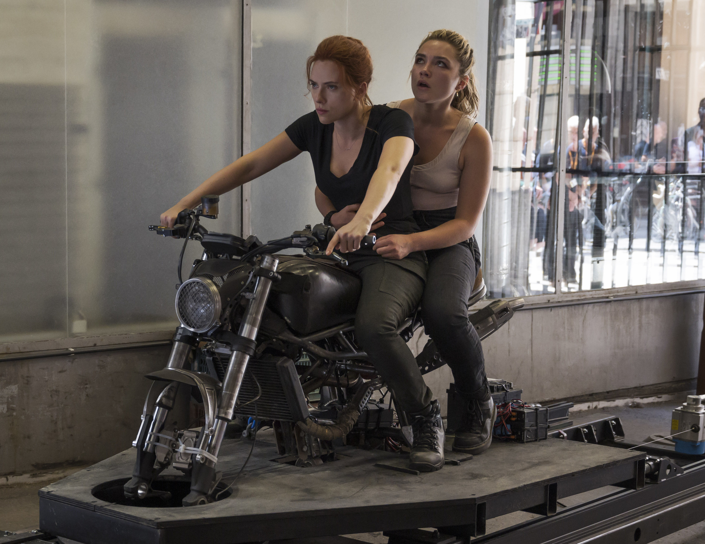 Scarlett and Florence sitting on a motorbike on a stand