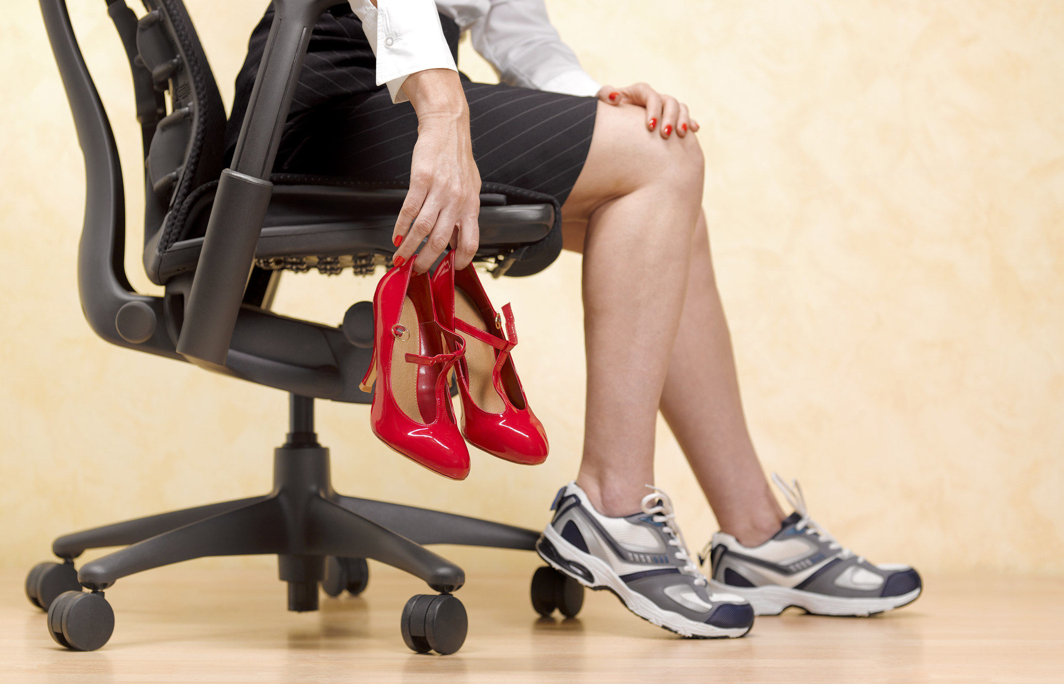 A woman in an office chair wearing tennis shoes and holding up a pair of high heels