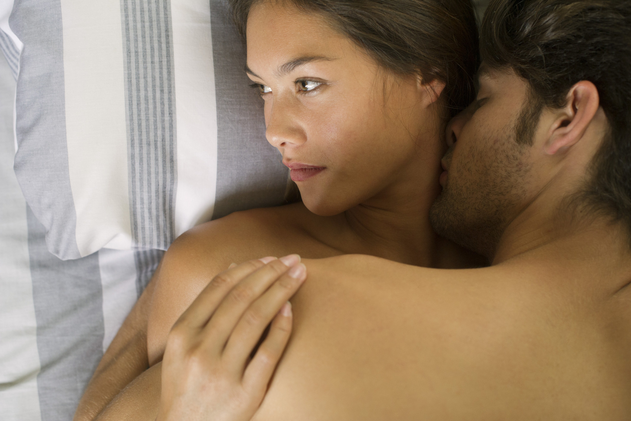 A woman in bed with a sexual partner kissing her neck