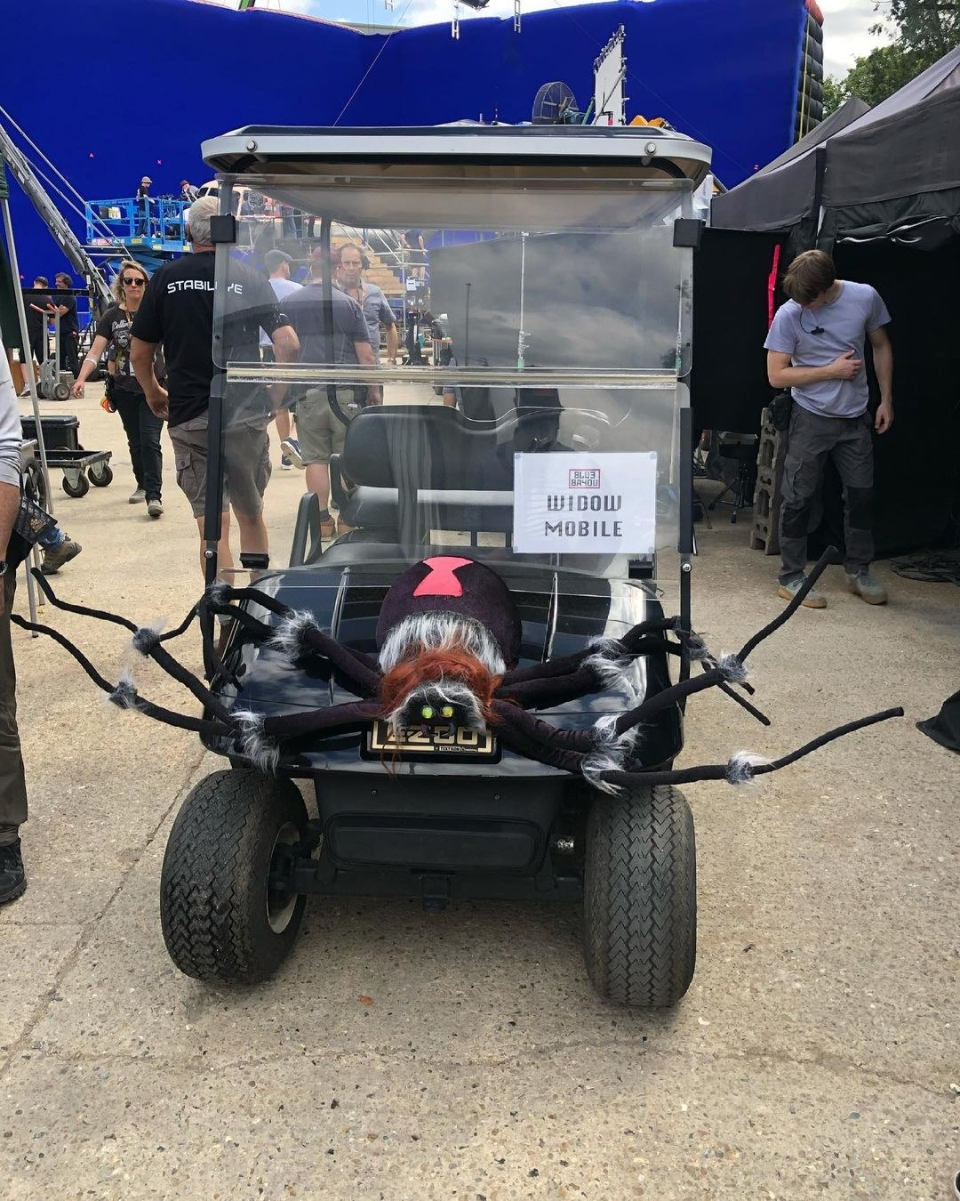 """A golf cart with a giant spider on the front called """"Widow Mobile"""""""