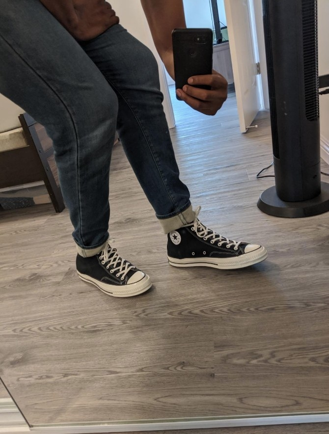Reviewer mirror photo of black high top converse