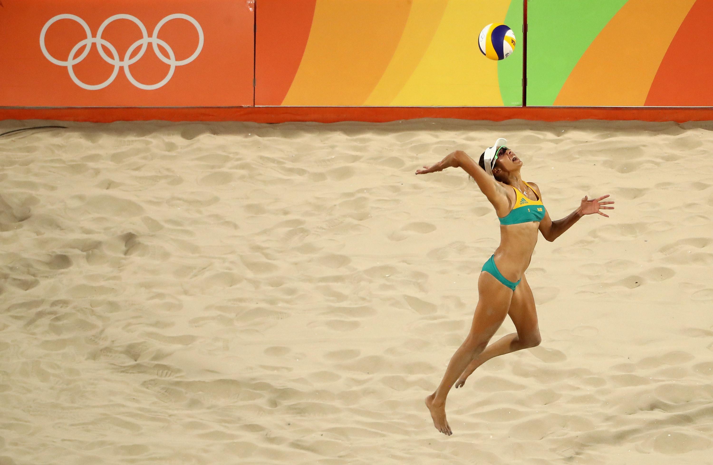 Woman serves beach volleyball