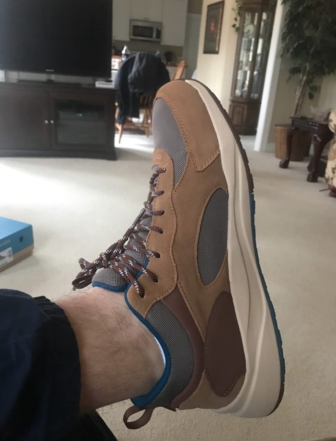 a reviewer wearing the hiking sneaker and in brown
