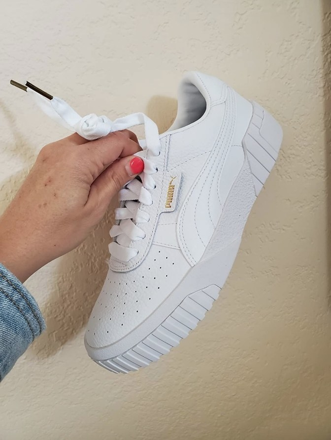 Reviewer holding all white Puma sneaker