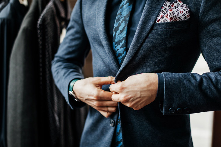 A close up of a man buttoning his suit