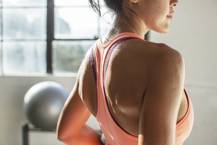 A sweaty woman working out in a sports bra