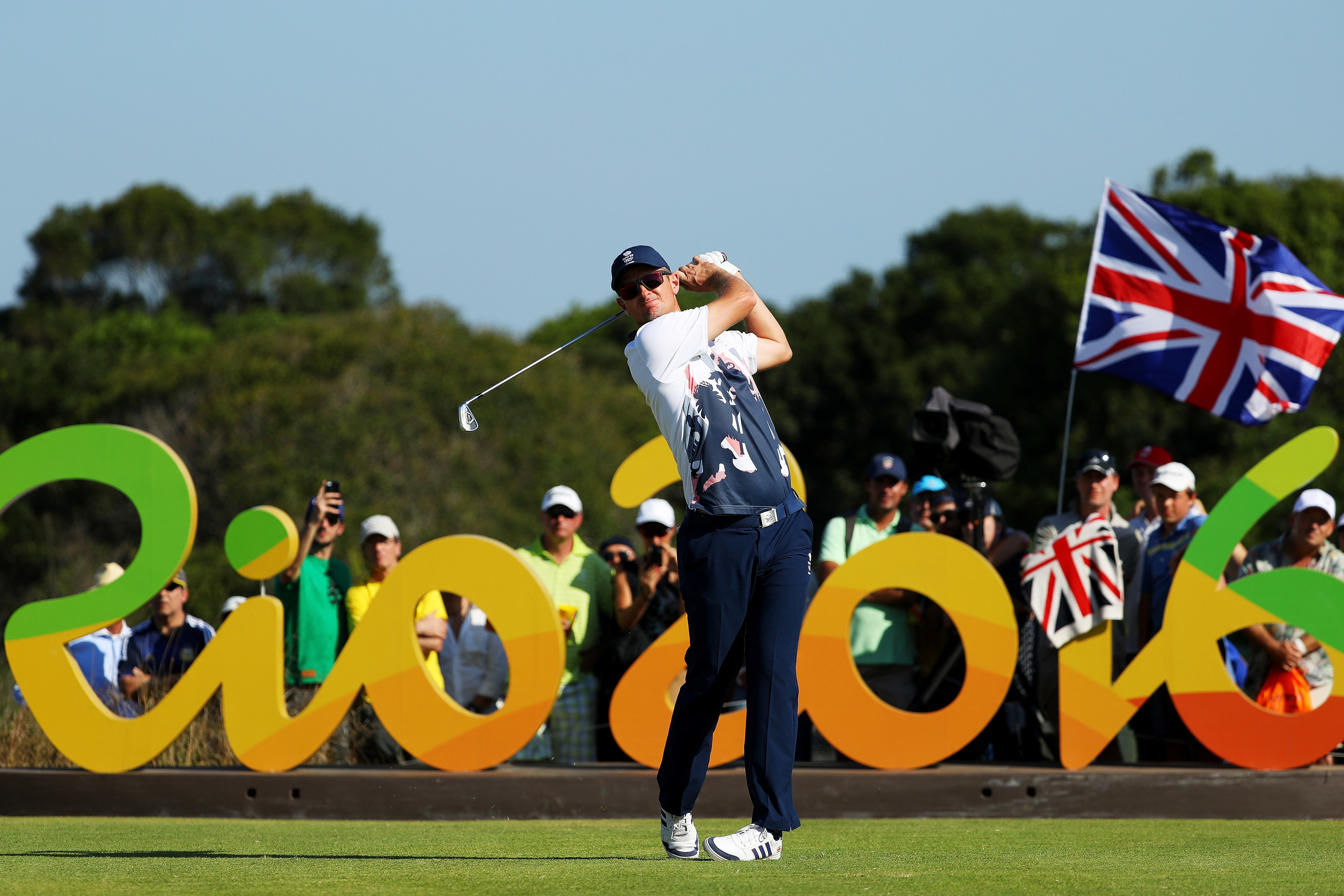 Man swings golf club in front of Rio 2016 sign