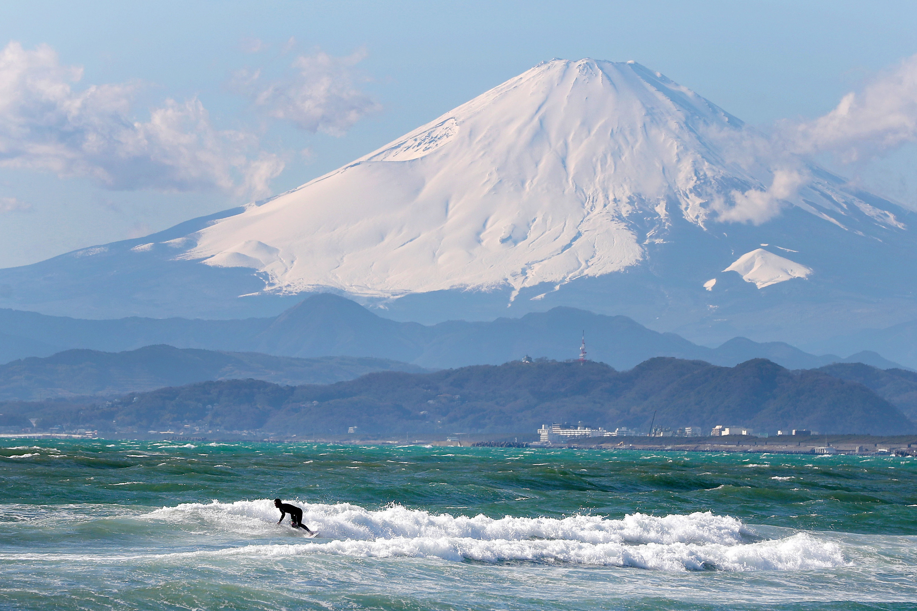 Surfer riding waves and a mountain in the backdrop