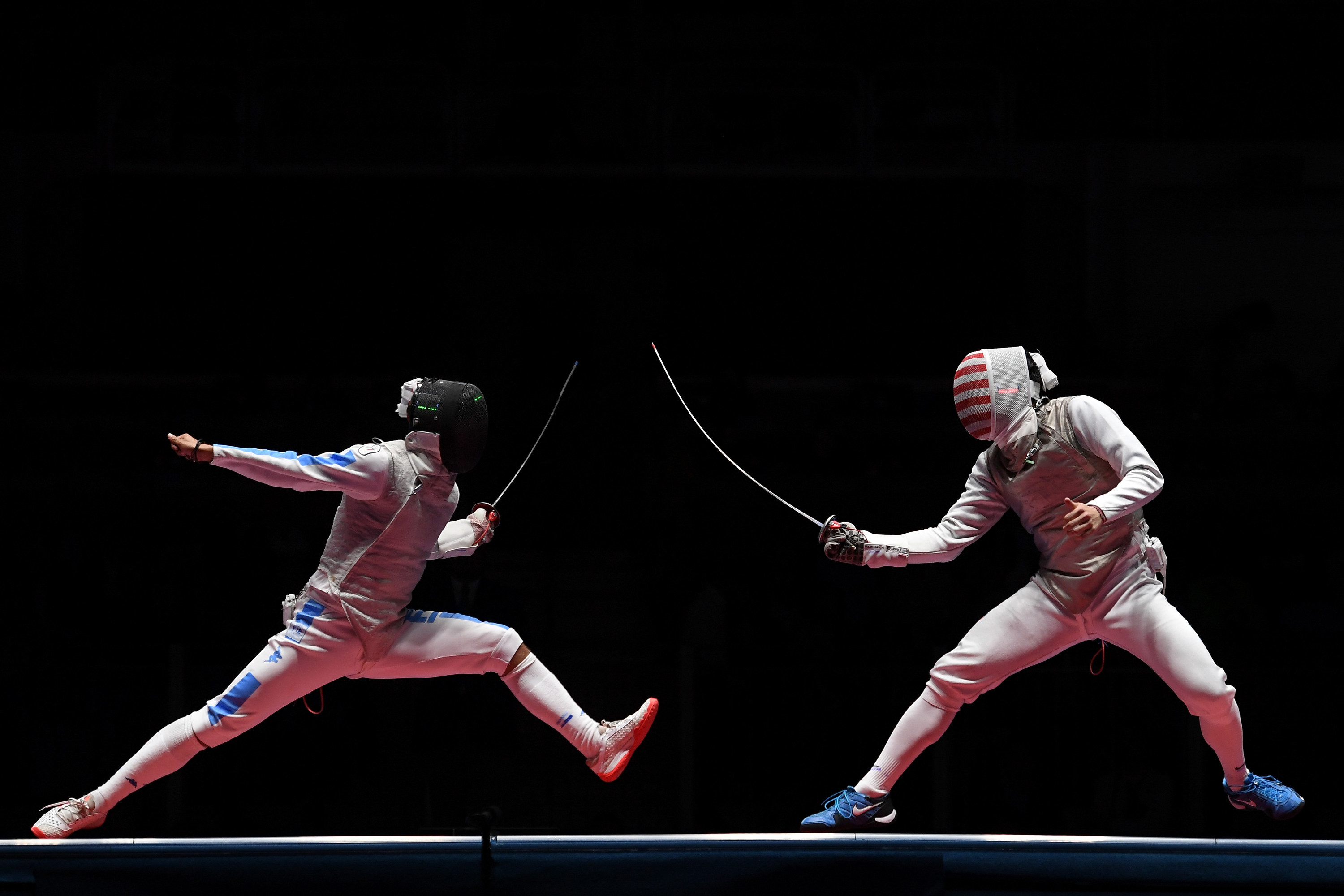 Two people fencing with thin swords