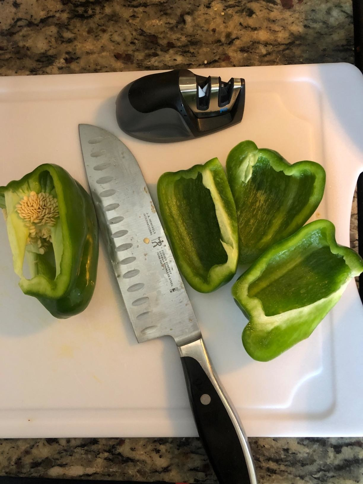 A reviewer photo of a knife next to sliced green peppers and the knife sharpener