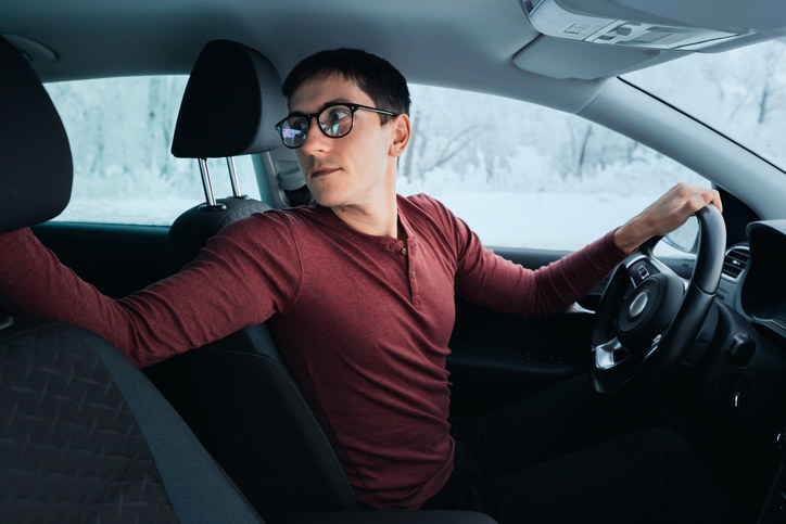 A nerdy man holding the passenger head rest so he can back up the car