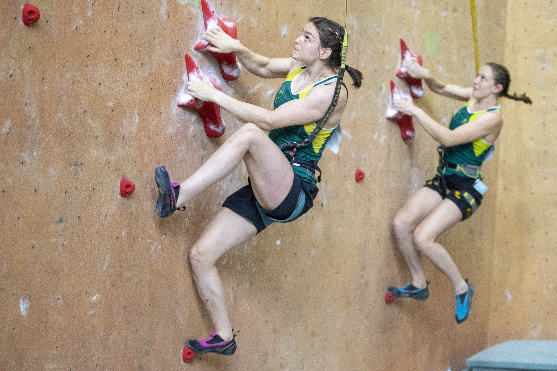 Two women scaling climbing wall