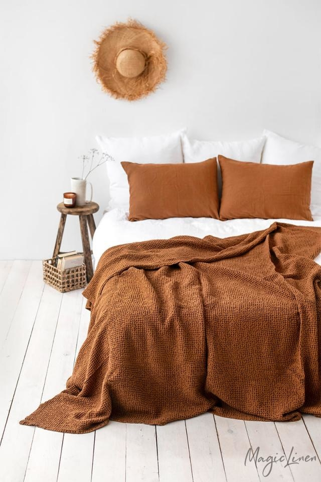 brown linen blanket on a bed with matching linen pillowcases on the pillows