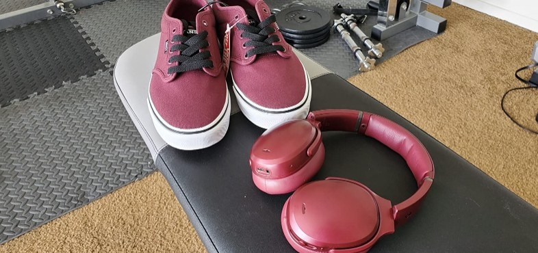 Red van low tops with black laces next to red headphones