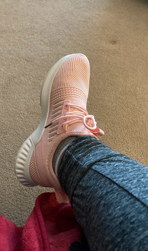 Pink running sneaker paired with blue leggings