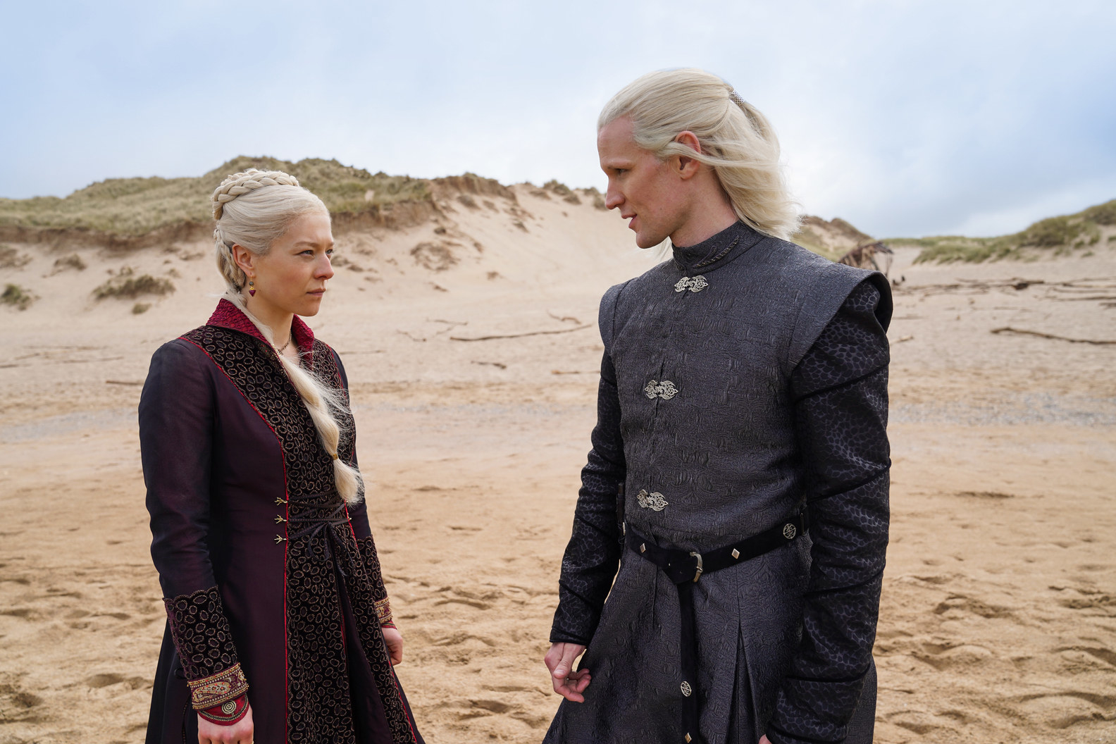 Two blonde characters speak to each other while standing in a sandy area