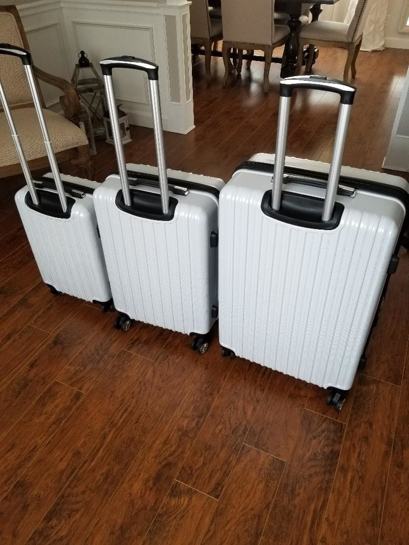 reviewer's three white suitcases of different sizes with the handles up