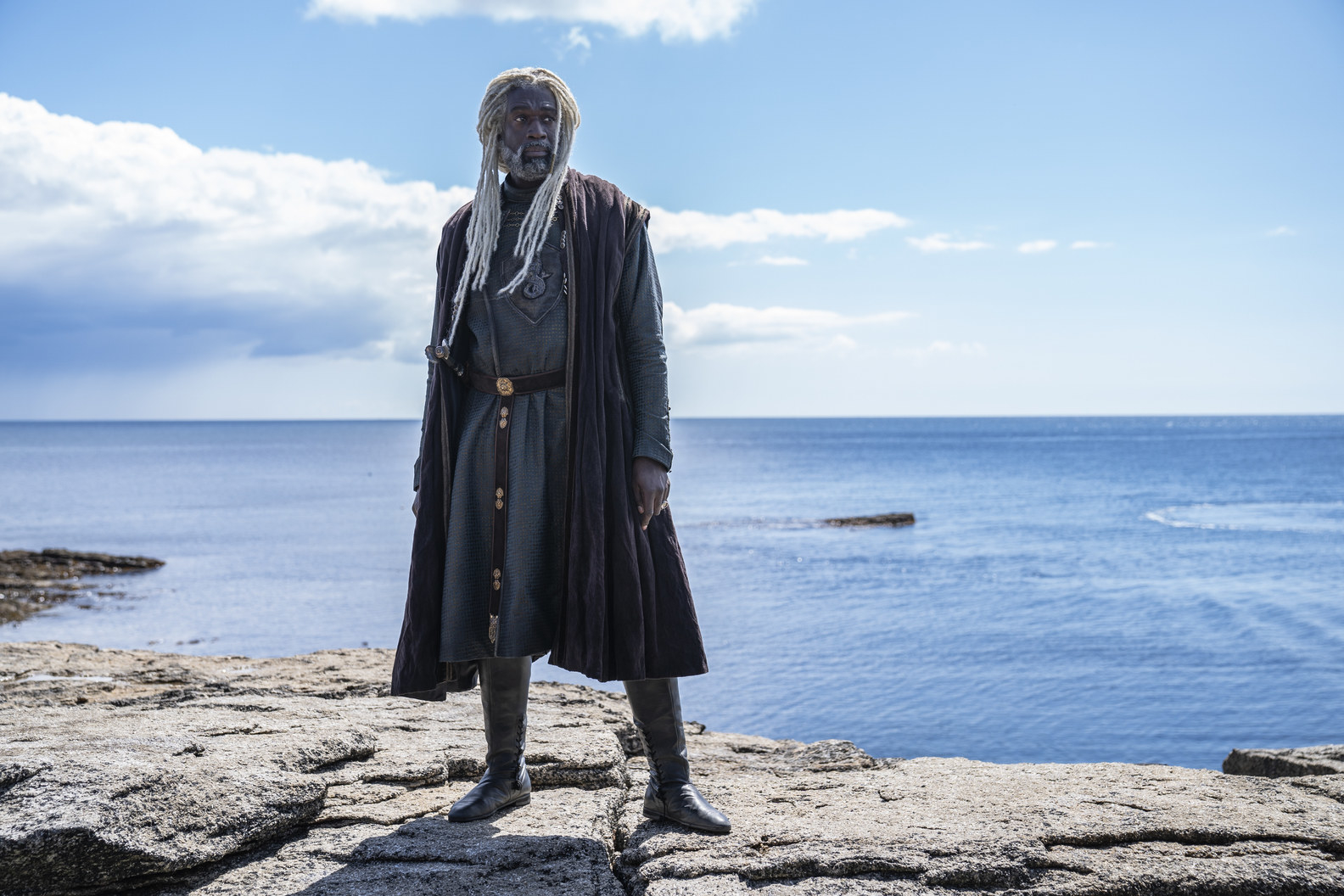 A character with long braided white hair and beard stands on a bluff in front of the ocean