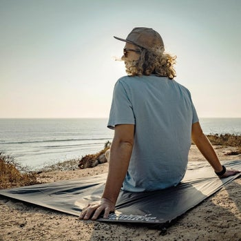 person sitting on the blanket while overlooking the ocean