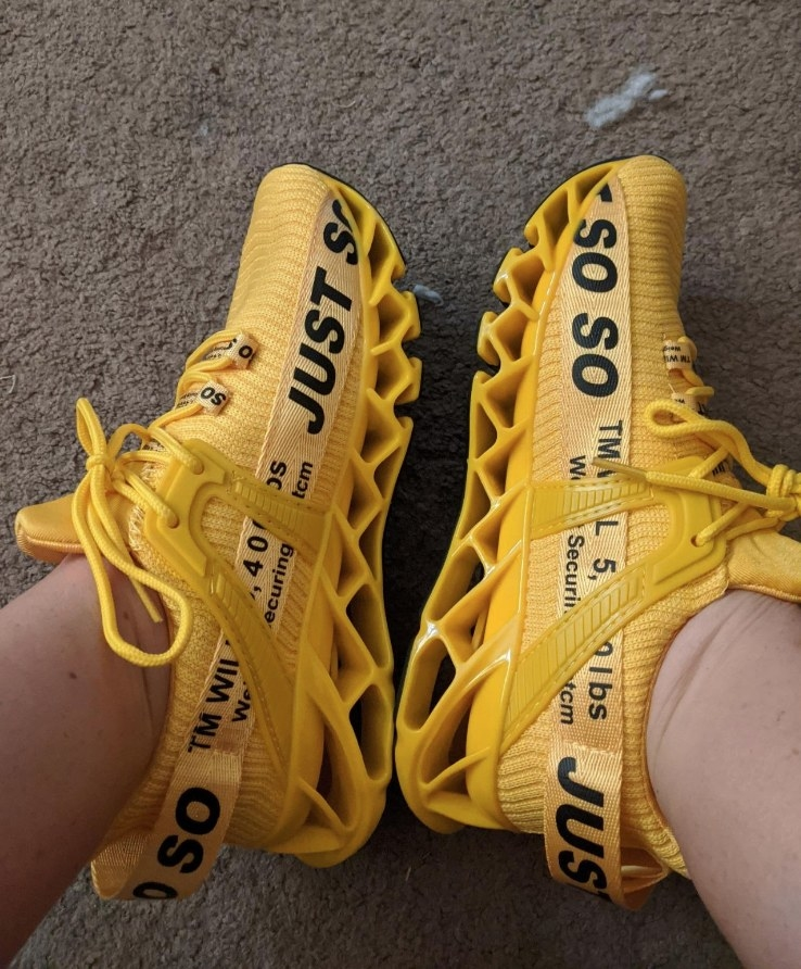 """Yellow sneakers with black words """"Just so"""" across upper body"""