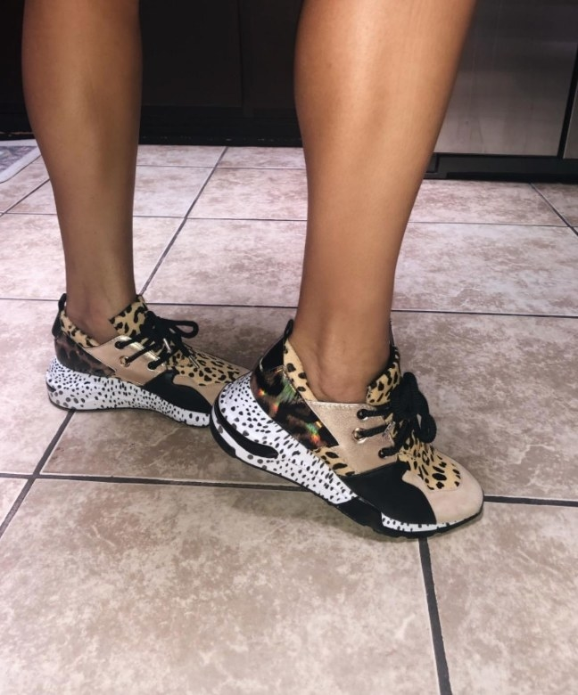 Reviewer wearing sneaker with leopard, gold and white/black polka dot print