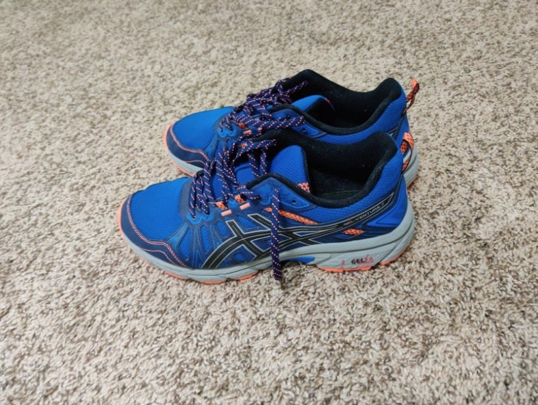 Blue running sneakers with black and orange detailing
