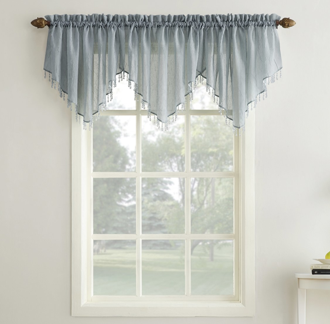 The light blue valance has beadings and three distinct sections