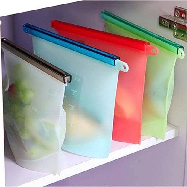 The silicone containers stored in a fridge with fruit and other leftovers in them