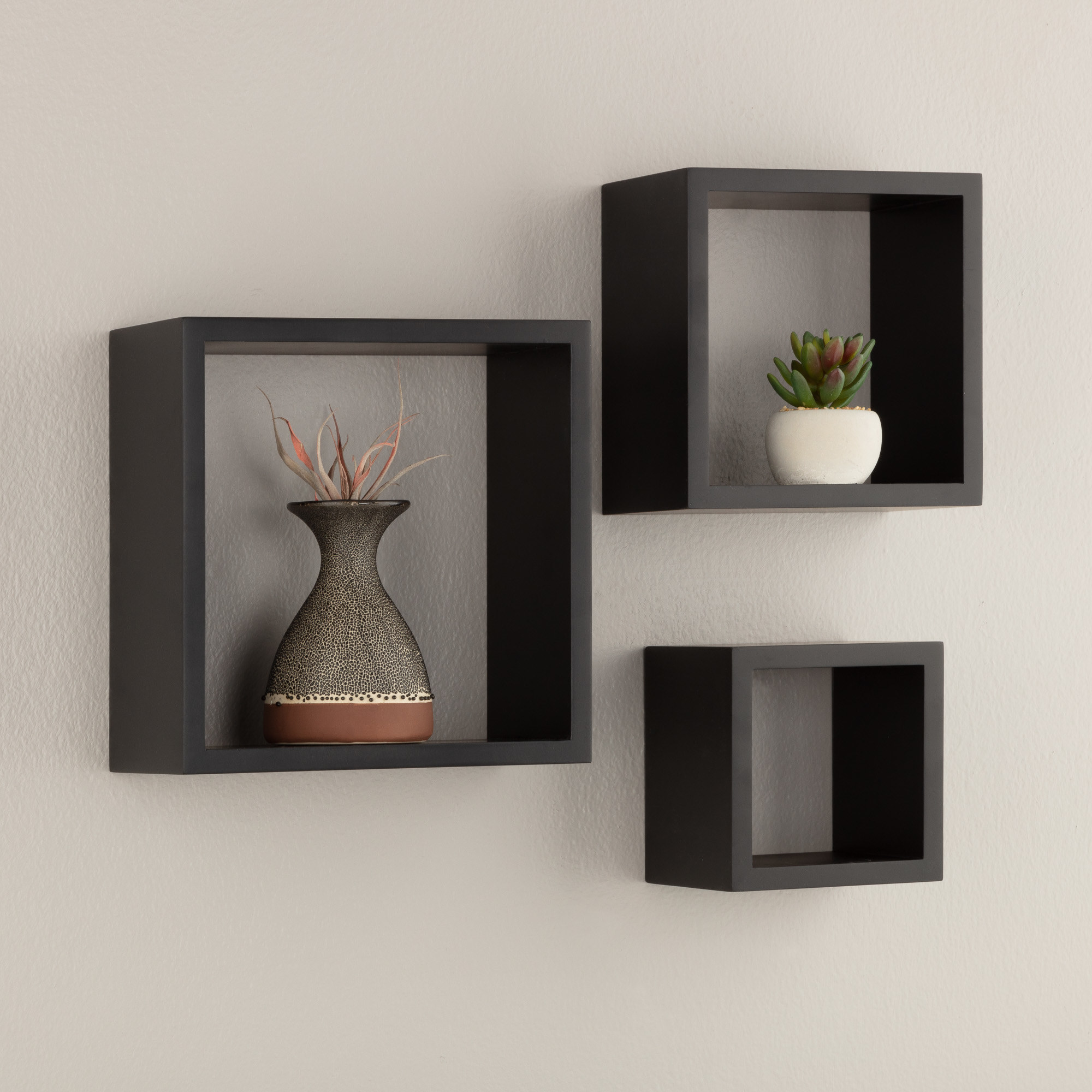Thethree-piece set of nested floating black wall cubes