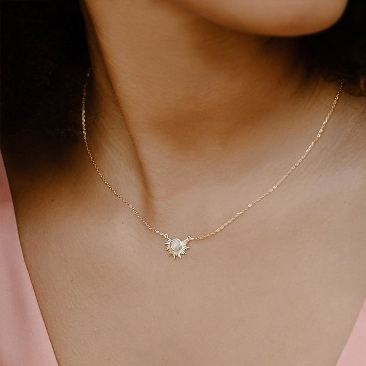 model wearing gold sunburst-style pendant necklace