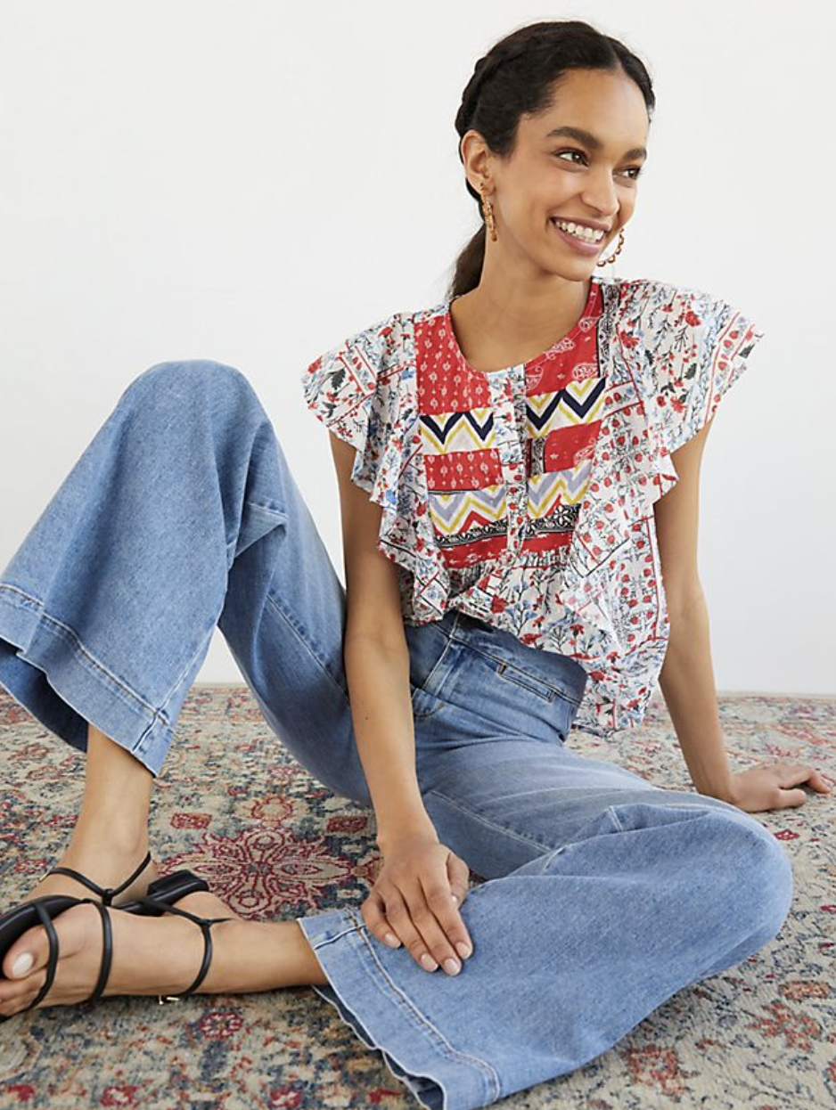 model in a white, red, blue, and yellow flutter sleeved t-shirt with bandana and paisley print
