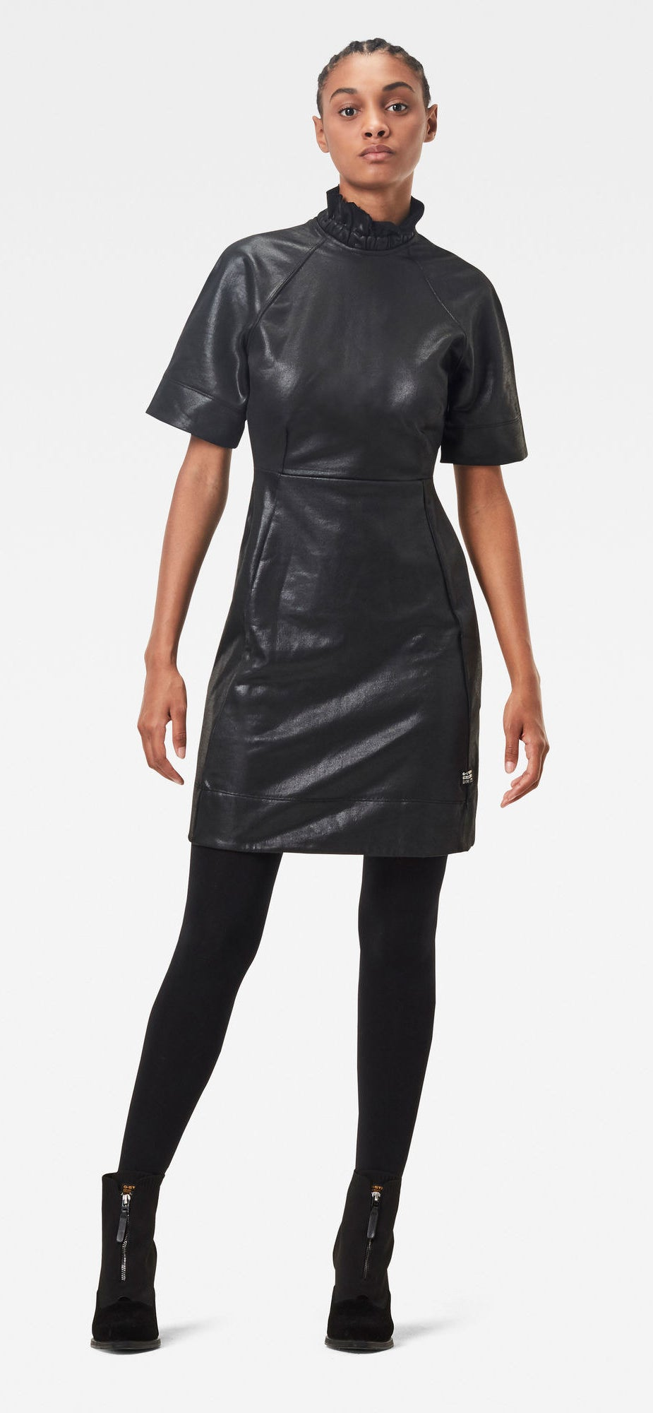 A model wears the glossy black dress