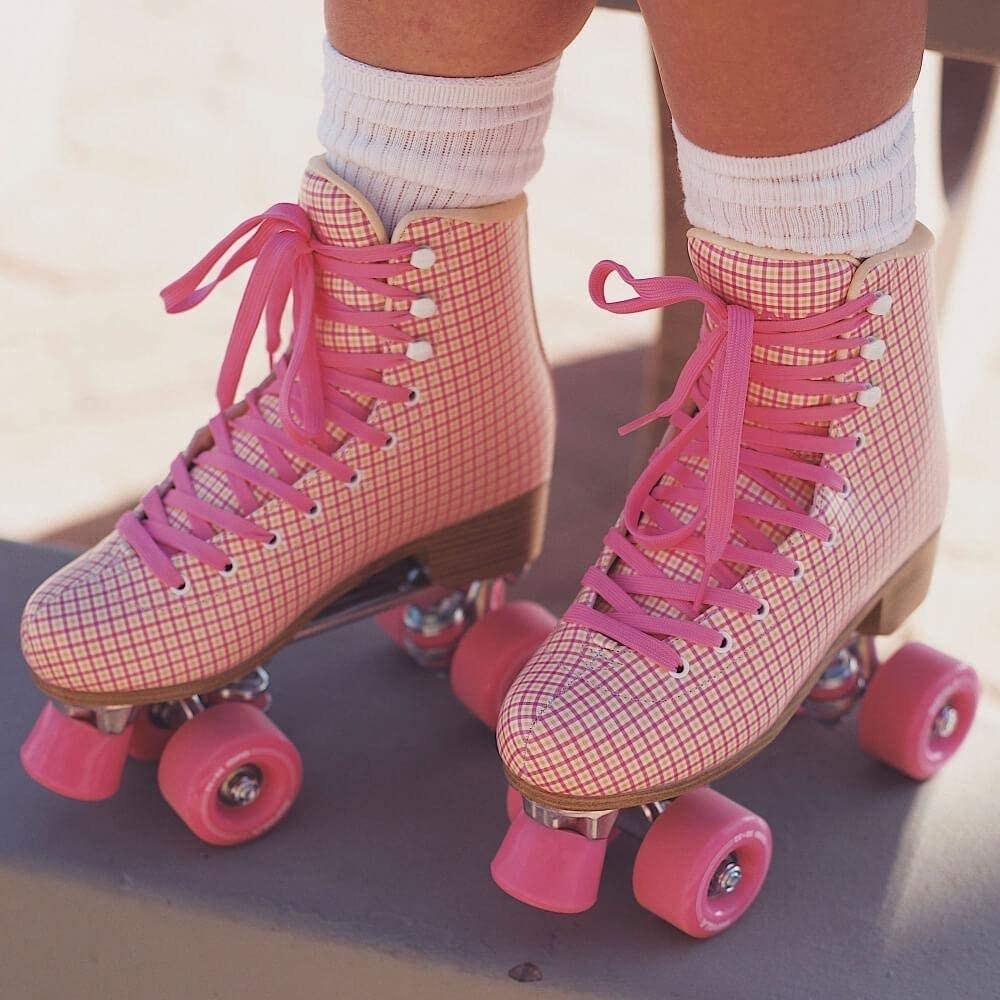 close up of a model wearing the pink tartan impala roller skates