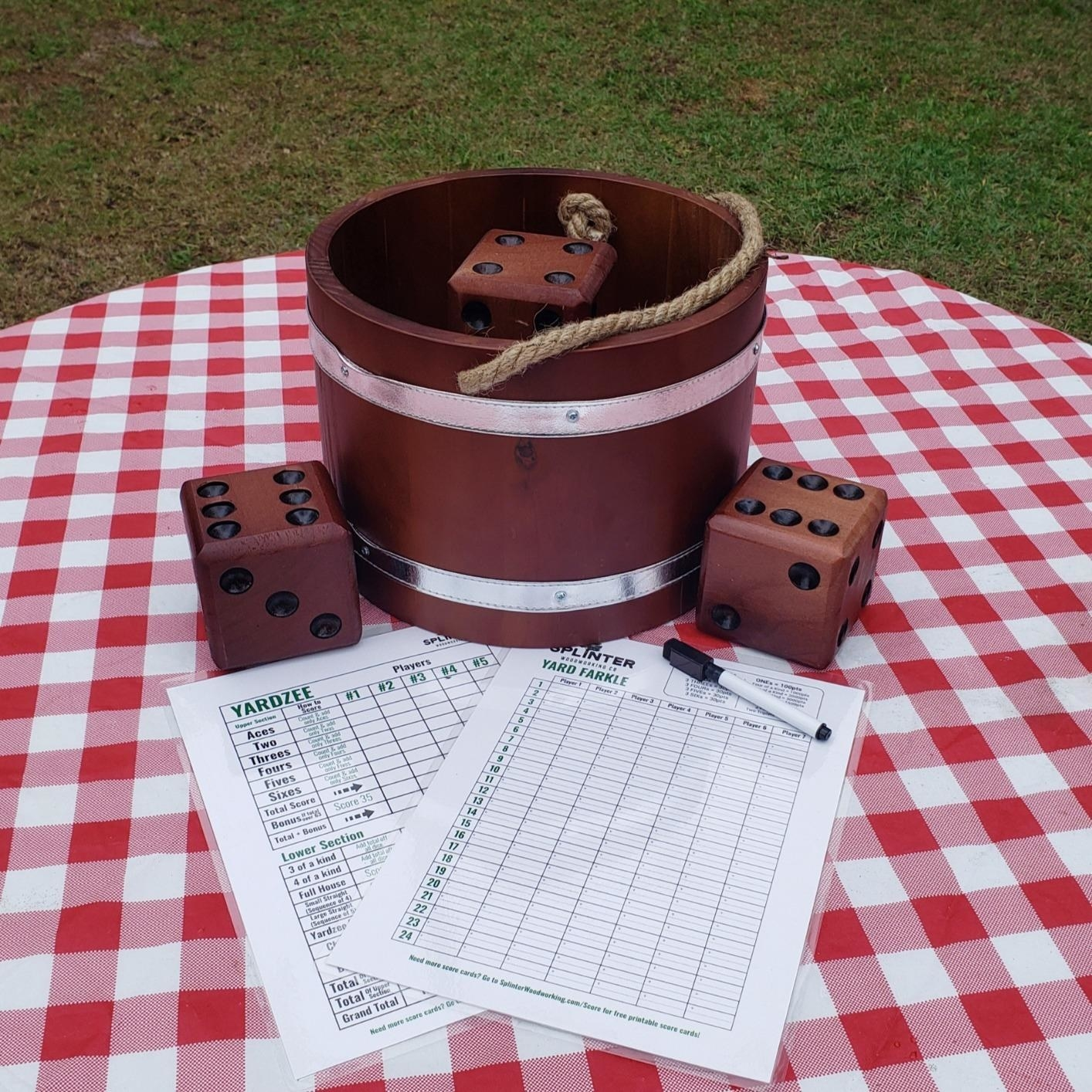 reviewer image of the giant dice, wooden bucket and score cards on a red gingham blanket outside