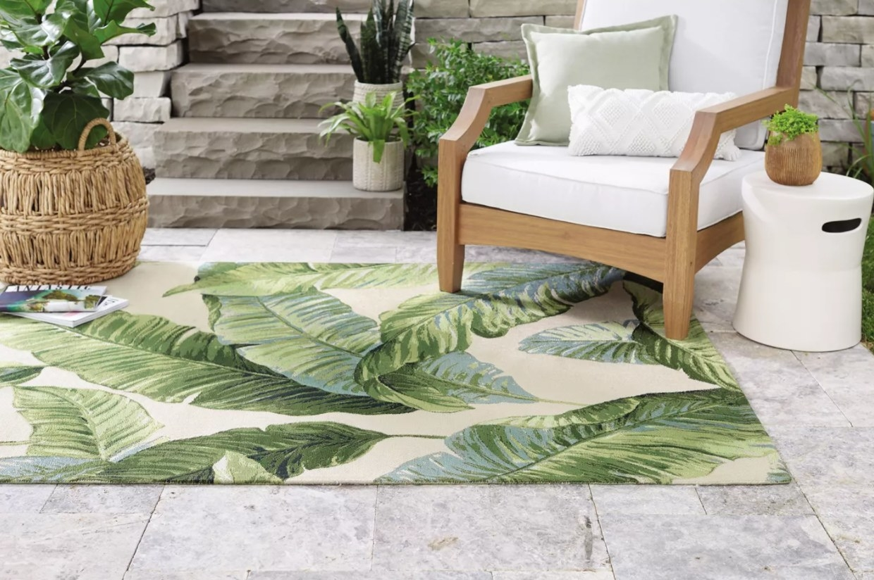 An outdoor rug with tropical greenery design