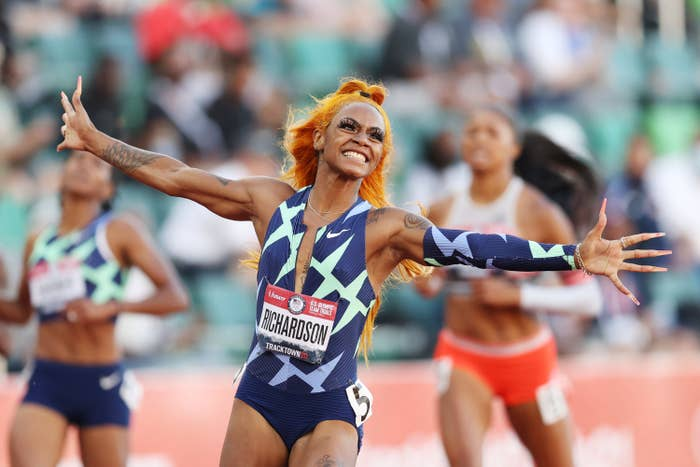 Sha'Carri, with arms raised and smiling, celebrates her performance in a race