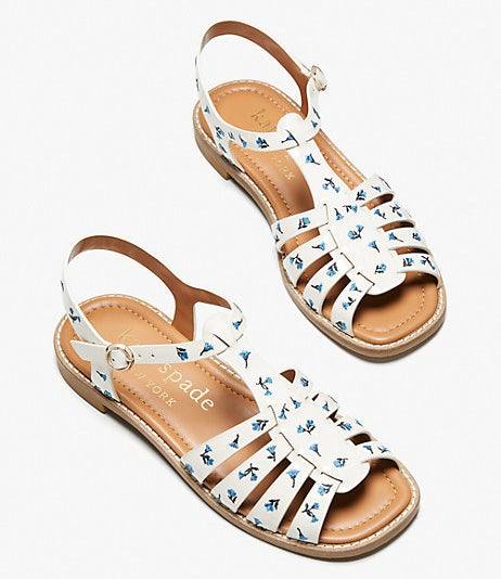 a pair of white leather sandals with a buckle ankle strap and a blue floral print