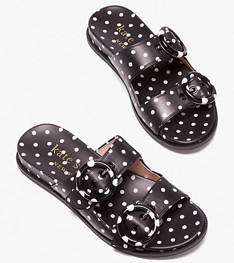 a pair of black slide with buckle details on the straps and a polka dot print