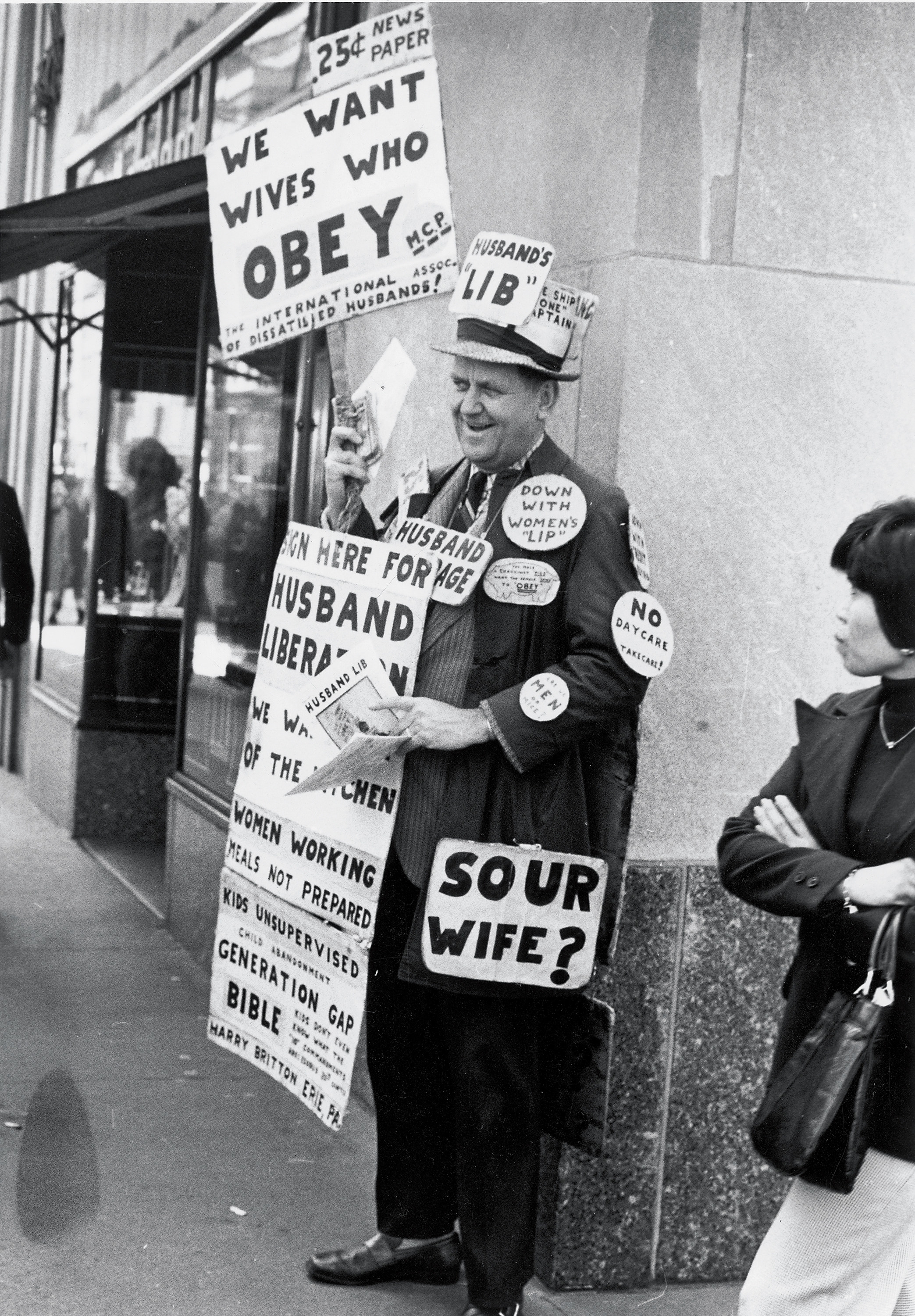 A man holding multiple signs including one that says sour wife with a question mark