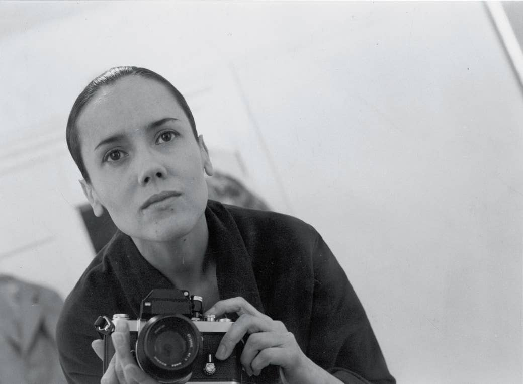 Self-portrait of woman holding camera in mirror