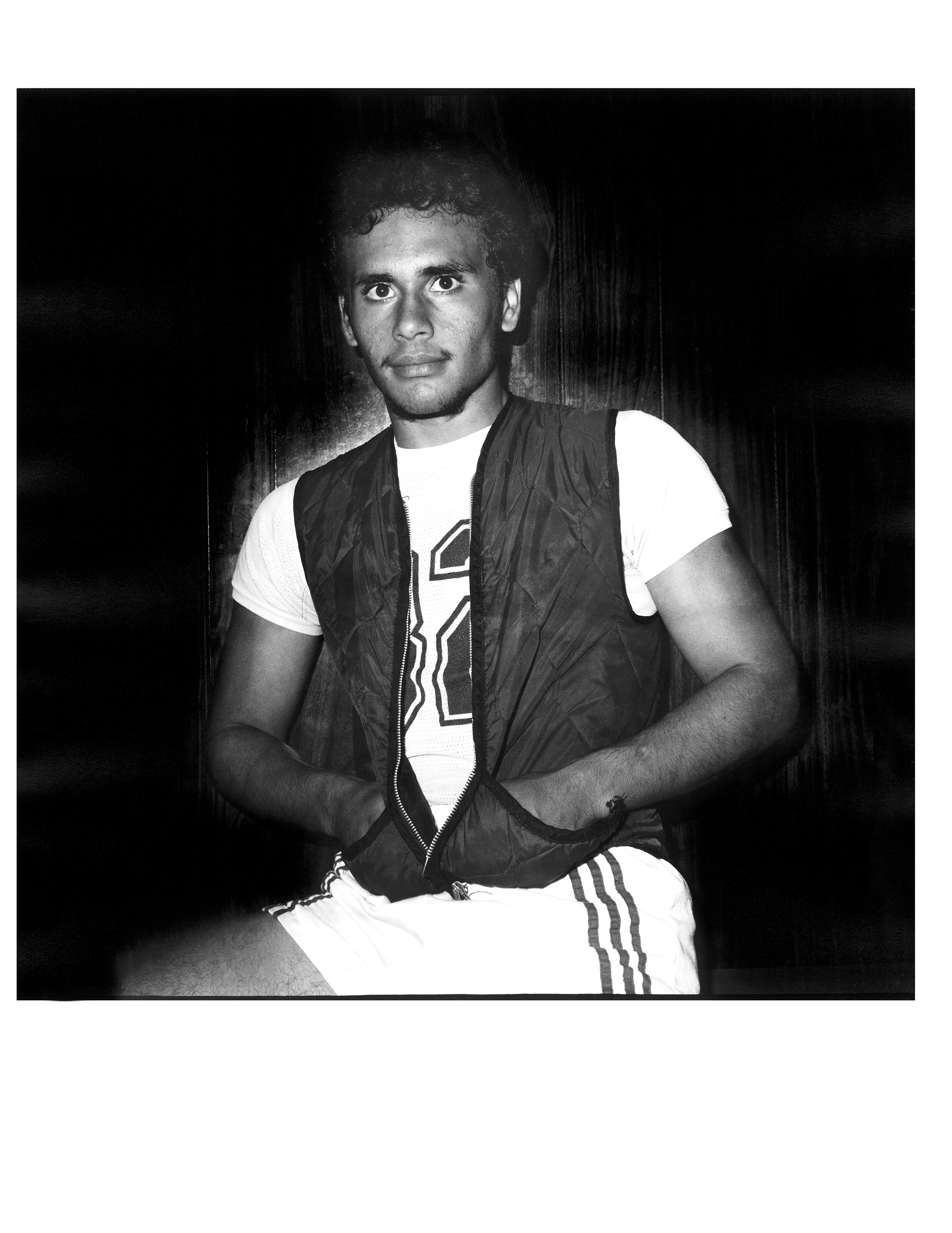 A young man in basketball shorts and a vest looking straight at the camera