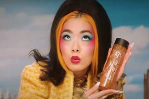 rina sawayama wears a lot of makeup and a furry jacket, looking upward, mouth in kiss position