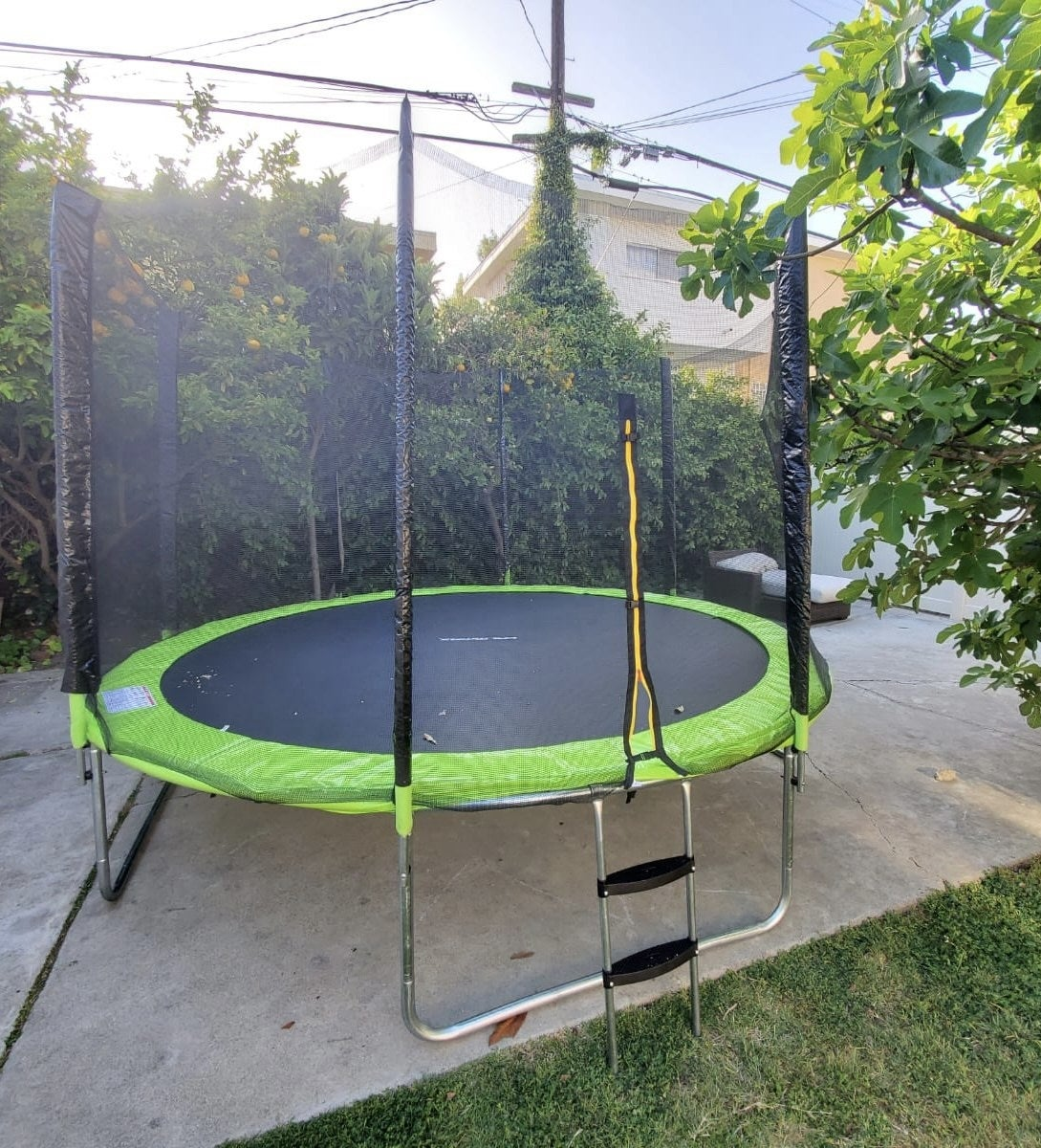 reviewer image of the green 12 foot trampoline in a backyard