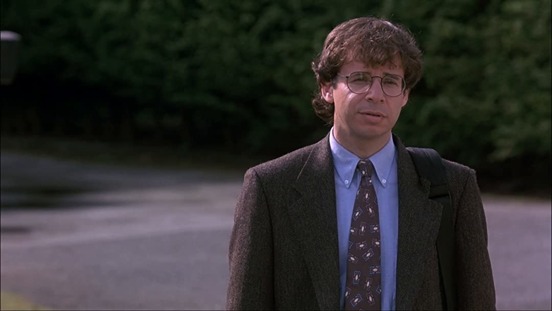 rick moranis in suit and tie, face relaxed