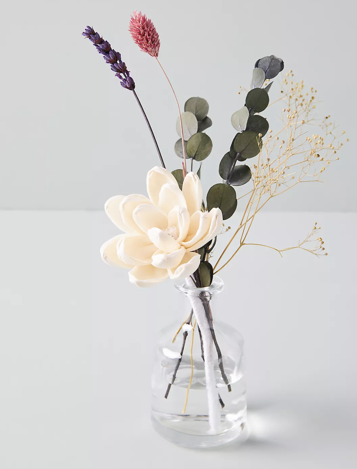 A clear small vase with flowers coming out of it