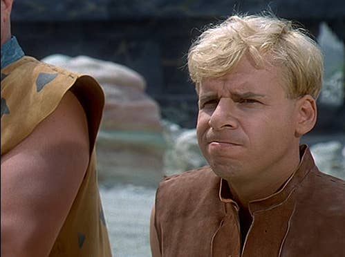 rick moranis as barney rubble with brows furrowed, mouth in a line