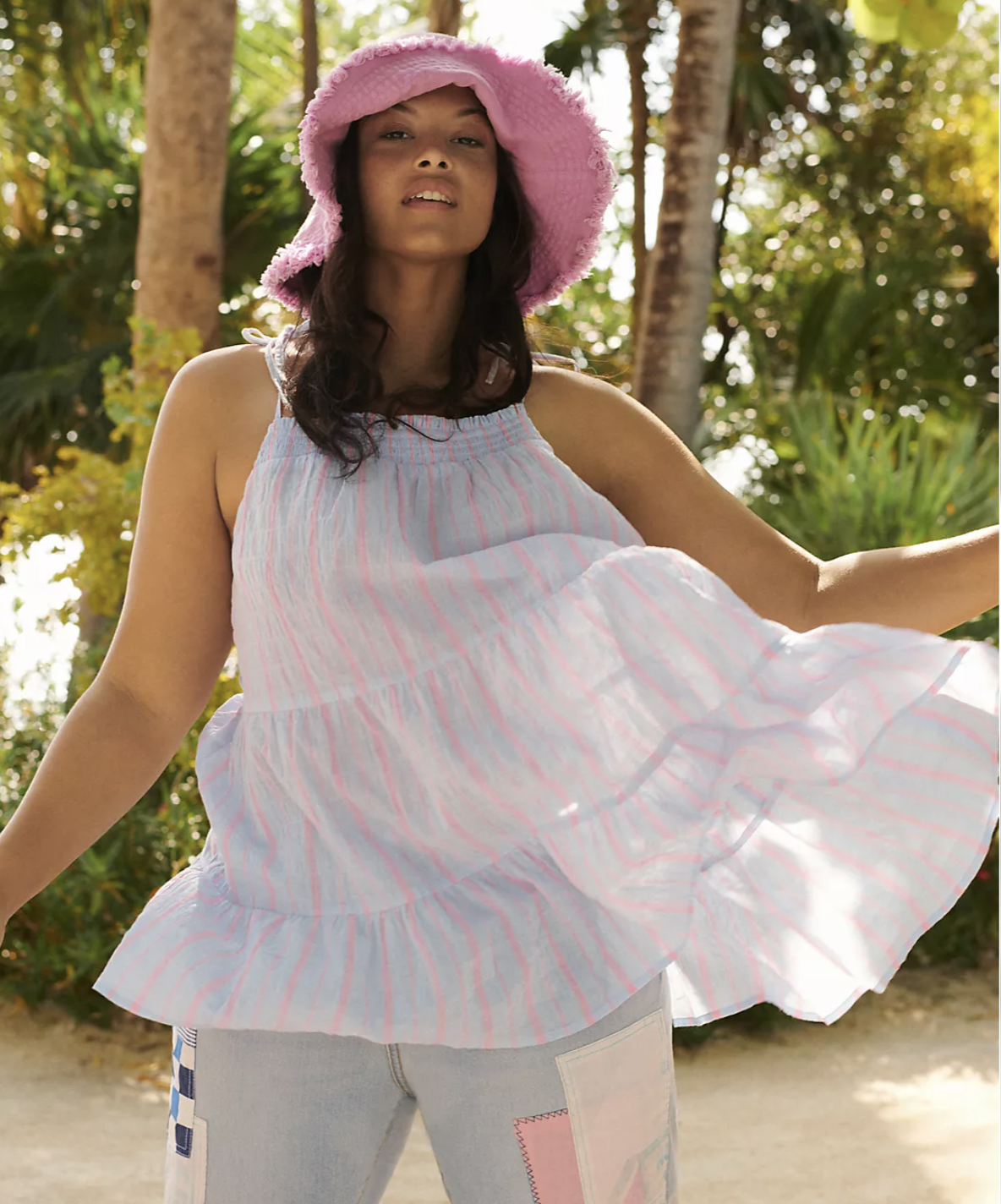Model in white tiered tunic length strappy top with pink stripes